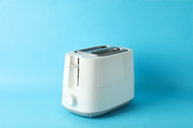 Toaster for bread on blue background, space for text