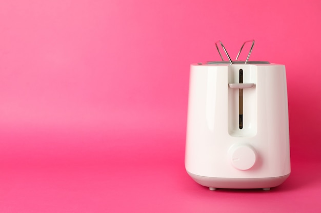 Toaster for bread on pink background, space for text