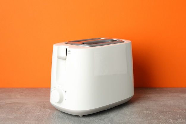 Toaster on grey table against orange background, space for text