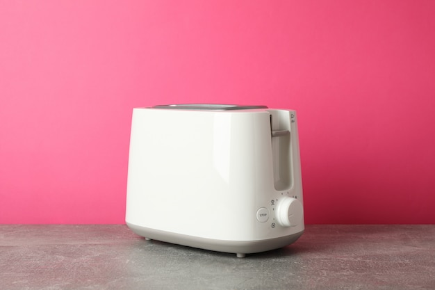 Toaster on grey table against pink background, space for text