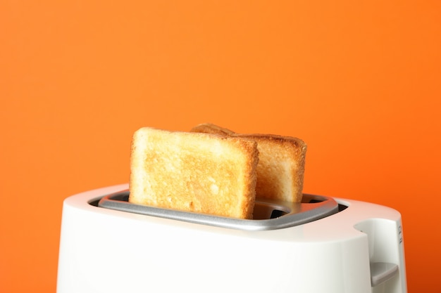 Toaster with bread on grey table against orange background, close up