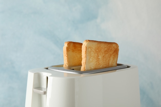 Toaster with bread slices on blue, space for text