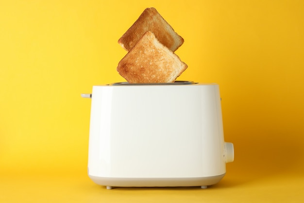 Toaster with bread slices on yellow background, space for text