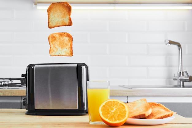 Тостер с блюдами и тост со свежим соком на деревянном кухонном столе