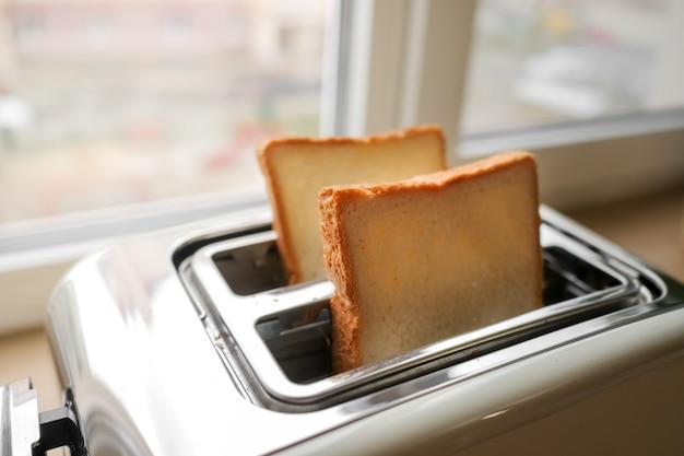 キッチンでパンのスライスを準備したトースター。ウィンドウで自宅で伝統的な朝食。セレクティブフォーカス