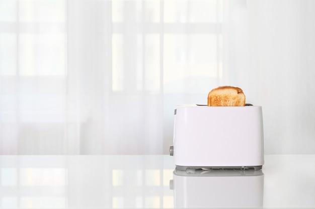 부엌 유리 테이블에 빵 조각을 얹은 토스터