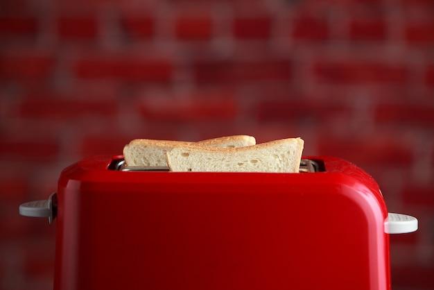 Тостер с поджаренным нарезанным хлебом на фоне стены кирпичей. кухонная утварь