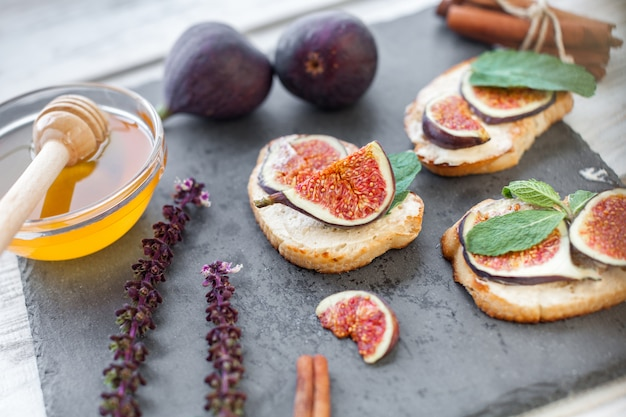Toasteres smeared by ricotta with figs and honey