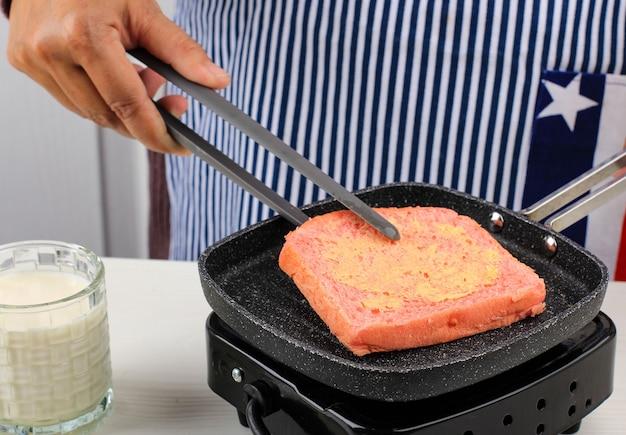 Поджаривание розового молочного хлеба хоккайдо для бутерброда. домохозяйка готовит завтрак для семьи с помощью элевтрической печи. розовый хлеб со сливочным маслом, подаваемый с молоком