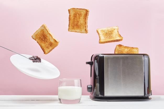 トースターからトースターが飛び出しました。浮揚食品、ジャム、皿。ピンクの背景においしい朝食。