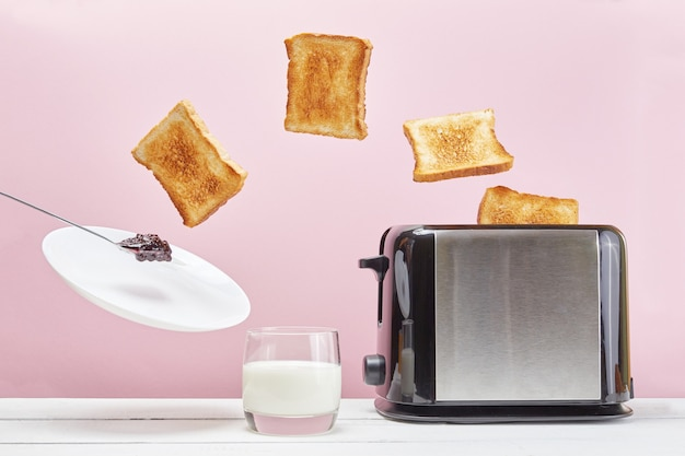 Toasts flew out of toaster. levitation food, jam and dish. delicious breakfast on pink background.