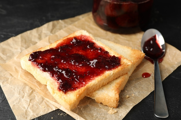 Toasts and glass jar with jam, spoon and baking paper on black background, close up