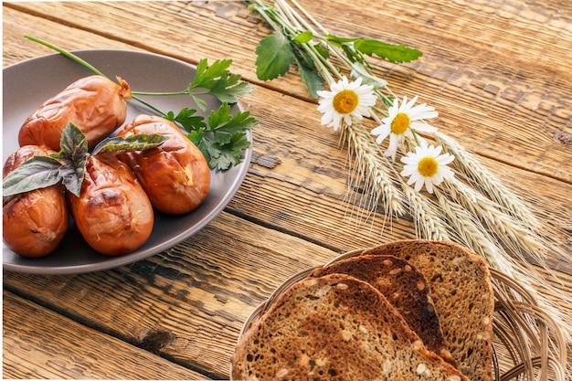 籐のかごで乾杯し、磁器の皿にバジルとパセリを添えたソーセージのグリル。木の板に小麦とカモミールの花の耳を持つ上面図。