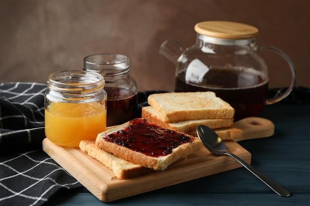 Тосты, джем и чай на деревянном фоне, крупный план