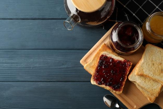 Тосты, джем и чай на деревянном фоне, вид сверху
