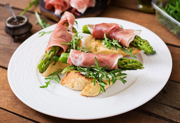 Toasts with asparagus, arugula and prosciutto