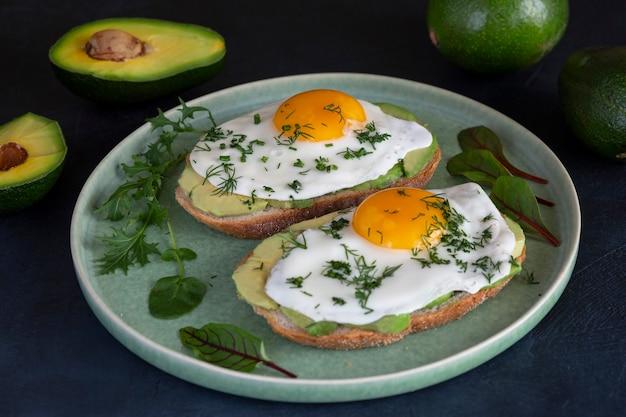 어두운 테이블 표면의 곡물 빵에 아보카도와 계란을 얹은 토스트 비타민 항산화 제와 섬유질이 풍부한 건강 식품