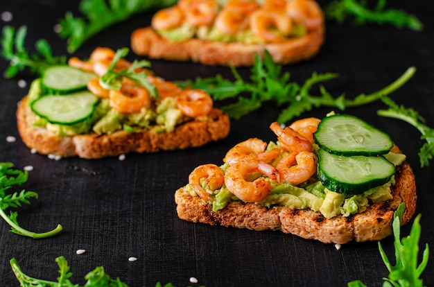 Toasts with avocado,fried shrimps, cucumber and arugula on black space. selective focus, close up