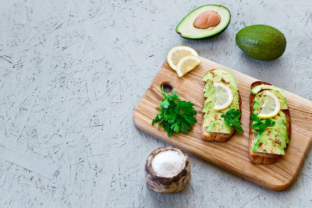 Toasts with avocado, lemon, chilli or paprika on a gray background