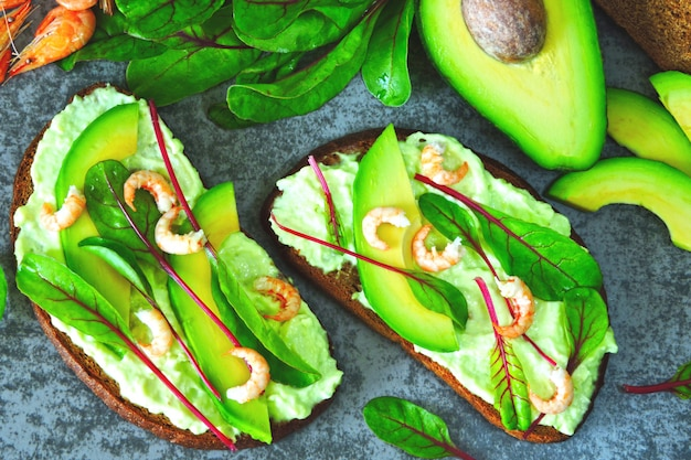 Toasts with avocado paste, prawns and chard. healthy eating. useful vegetarian open sandwiches with avocado and shrimp. salad chard. vegetarian foods. superfoods.