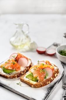 Toasts with avocado, radish and salmon. healthy eating