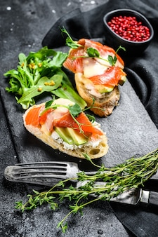 Toasts with avocado and smoked salmon. black background. top view.