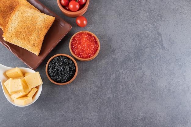 버터와 빨간 체리 토마토 토스트는 대리석 배경에 배치됩니다.