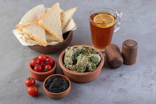 Гренки со сливочным маслом и красными помидорами черри на мраморной поверхности.