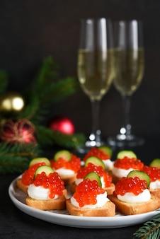 샴페인과 함께 새해 테이블에 치즈와 빨간 캐비어와 토스트. 새해 테이블. 간식.