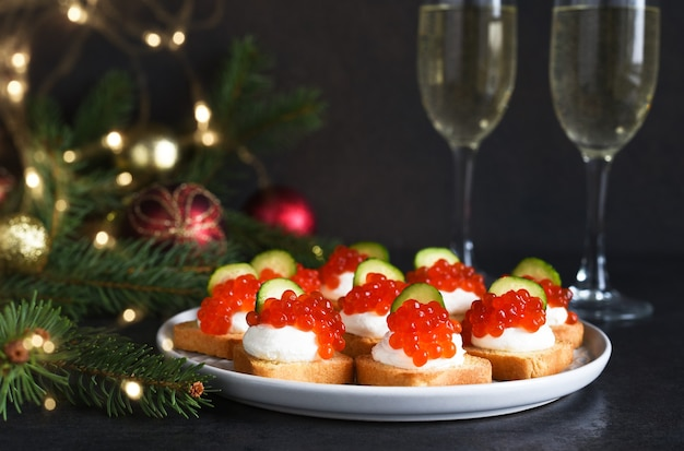 Toasts with cheese and red caviar on a new year's table with champagne. new year's table. snack.