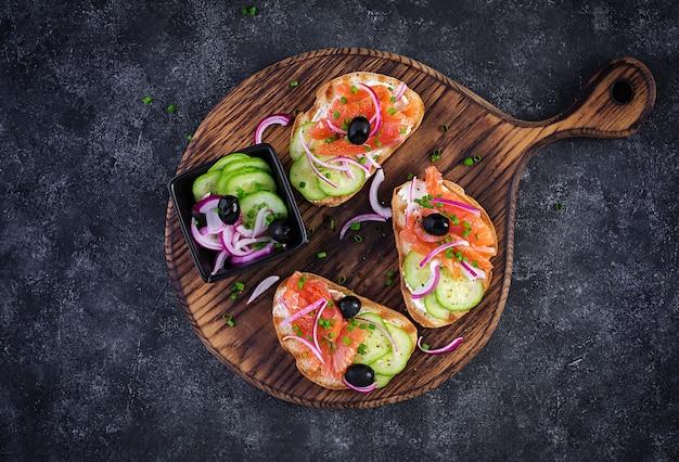 Тосты со сливочным сыром, копченым лососем, огурцом и красным луком на темном столе. открытые бутерброды. здоровый уход, концепция супер питания. вид сверху, сверху