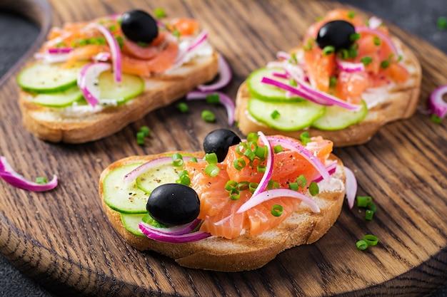Тосты со сливочным сыром, копченым лососем, огурцом и красным луком на темном столе. открытые бутерброды. здоровый уход, концепция супер питания.