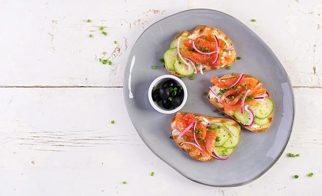 Тосты со сливочным сыром, копченым лососем, огурцом и красным луком на деревенском деревянном столе. открытые бутерброды. здоровый уход, концепция супер питания. вид сверху, сверху