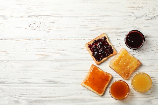 Toasts with delicious jams on wooden background, top view