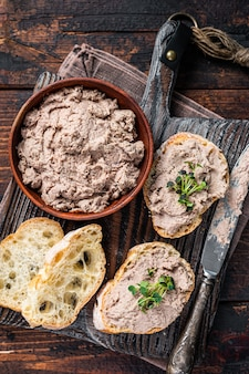 나무 판자에 오리 파테 rillettes de canard를 곁들인 토스트. 어두운 나무 배경입니다. 평면도.