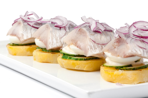 Toasts with herring appetizer on white background close up