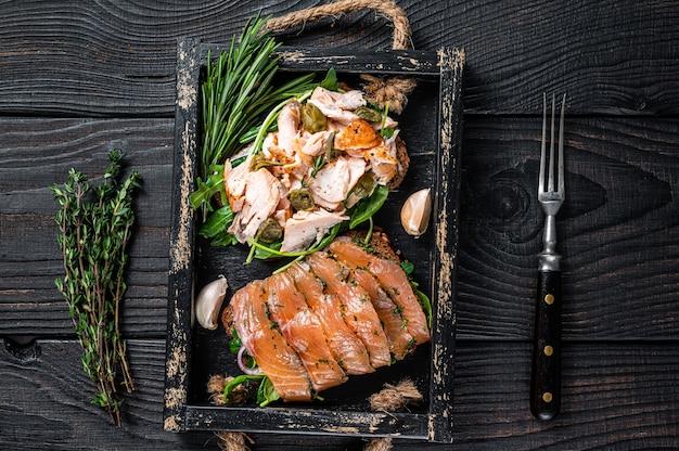 Тосты с лососем горячего и холодного копчения, рукколой на деревянном подносе с зеленью