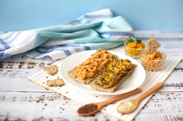 白い木製の背景にフムスとトースト。クラッカーにひよこ豆のペースト。ベジタリアン料理のコンセプト