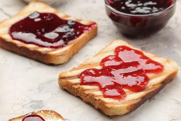 잼 토스트. 가벼운 콘크리트 테이블에 빨간 잼을 곁들인 바삭한 토스트 튀김. 아침밥. 확대