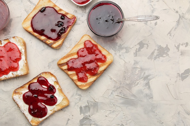 Гренки с джемом. жареные хрустящие тосты с красным джемом на светлом бетонном столе. завтрак. вид сверху