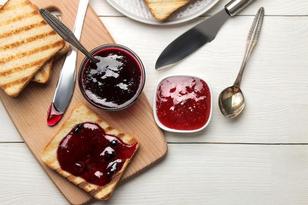 Гренки с джемом. жареные хрустящие тосты с красным джемом на белом деревянном столе. завтрак. вид сверху