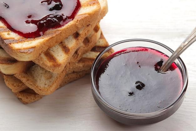 잼 토스트. 흰색 나무 테이블에 빨간 잼 튀김 된 바삭한 토스트.