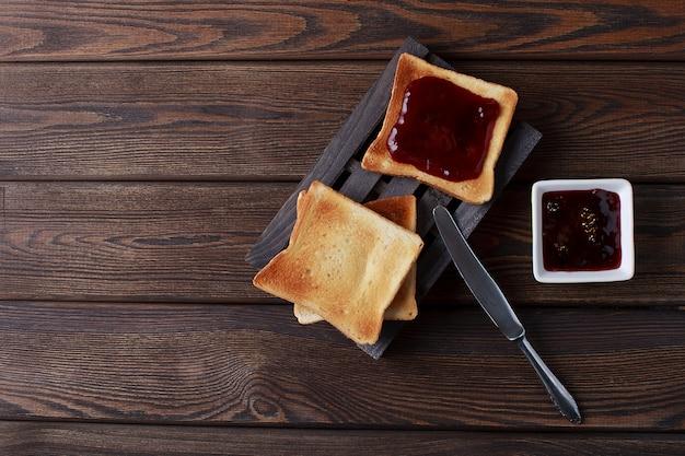 Тосты с джемом на темном деревянном столе