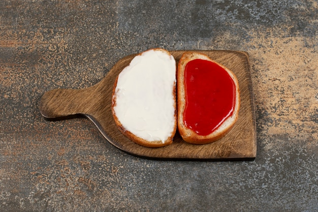 Toast con marmellata e panna acida su tavola di legno.
