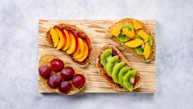 Тосты с арахисовым маслом, клубничным джемом, бананом, виноградом, персиком, киви, ананасом, орехами