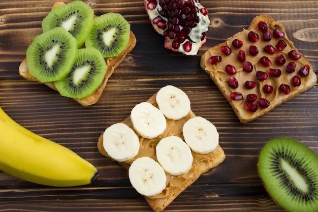 木の表面にピーナッツペーストとフルーツを添えたトースト