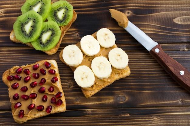 木の表面にピーナッツペースト、フルーツ、ナイフで乾杯