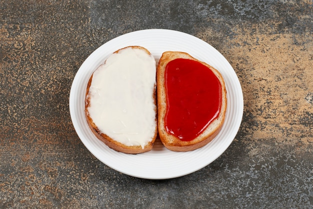 Тосты с клубничным вареньем и сметаной на белой тарелке.