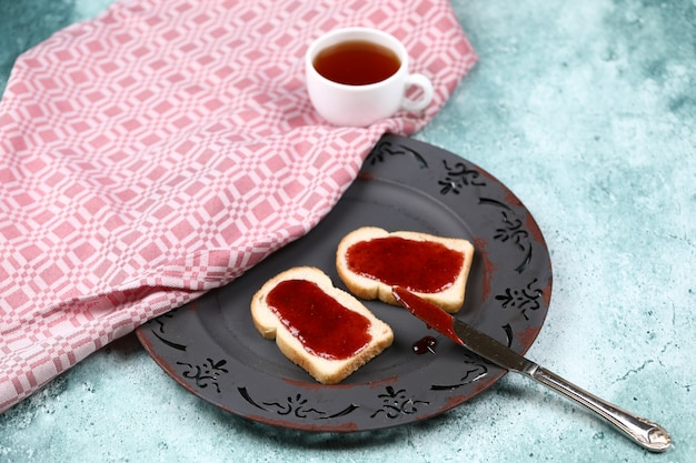 Toasts with strawberry jam and a cup of tea.