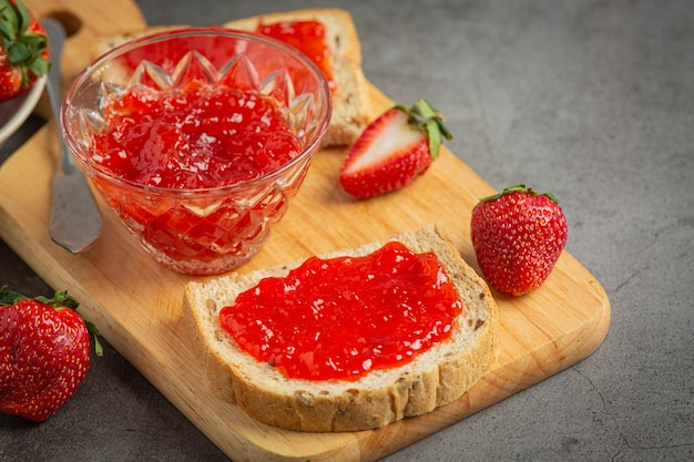 Toasts with strawberry jam on old dark background